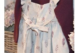 Pichi gris con plumas moradas y jersey morado con volantito de plumeti blanco en los puños y cuello.